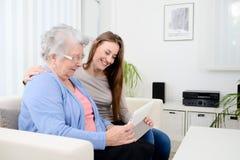 Chica joven alegre que comparte tiempo con una vieja mujer mayor y que enseña a Internet con una tableta del ordenador Imagen de archivo