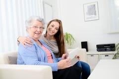Chica joven alegre que comparte tiempo con una vieja mujer mayor y que enseña a Internet con una tableta del ordenador Foto de archivo