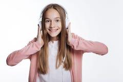 Chica joven alegre que escucha la música en auriculares Foto de archivo