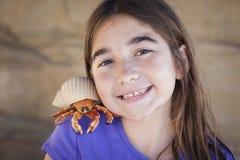 Chica joven alegre que juega con Toy Hermit Crab Fotografía de archivo