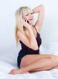 Chica joven alegre que llama por teléfono y que se sienta en cama Foto de archivo