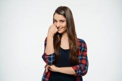 Chica joven alegre que presenta sobre el fondo blanco que mira la cámara Foto de archivo libre de regalías