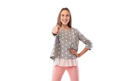 Chica joven alegre que señala en usted que se coloca en una actitud confiada Foto de archivo libre de regalías