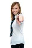 Chica joven alegre que señala hacia la cámara Imagen de archivo libre de regalías