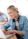 Chica joven alegre que trabaja en el ordenador portátil con los auriculares Foto de archivo libre de regalías