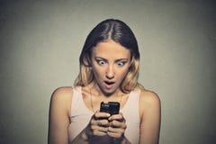 Chica joven ansiosa que mira el teléfono que ve malas noticias Fotografía de archivo libre de regalías
