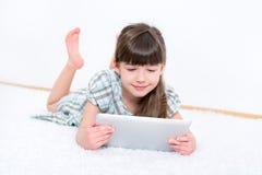 Niño con el ordenador de la tableta del ipad de la manzana Imagen de archivo libre de regalías
