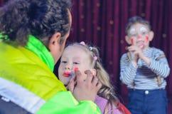 Chica joven aplicada con el payaso Makeup por un artista Imágenes de archivo libres de regalías