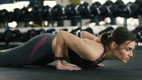 Chica joven apta que hace los execrises en gimnasio, pectorales, almacen de metraje de vídeo