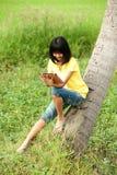 Chica joven asiática de Pertty en la tablilla. fotografía de archivo