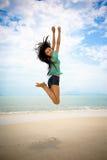 Chica joven asiática feliz que salta agraciado Imagenes de archivo