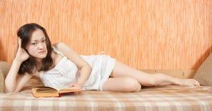 Chica joven asiática que se reclina sobre el sofá Fotografía de archivo