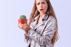 Chica joven asombrosa que presenta con el cactus en un fondo gris Imagen de archivo