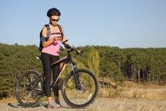 Chica joven atlética en una bicicleta en viaje turístico Fotografía de archivo libre de regalías