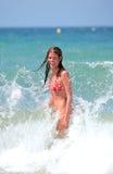 Chica joven atractiva atractiva que es salpicada por la onda fría en el SE Fotos de archivo libres de regalías