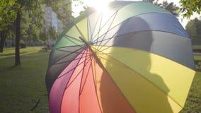 Chica joven atractiva con el paraguas multicolor que da vuelta y que mira a la cámara que sonríe en el parque Ocio del verano almacen de metraje de vídeo