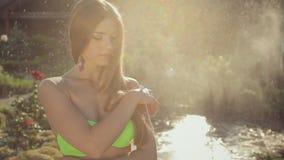 Chica joven atractiva con el pelo largo que lleva un bikini adentro almacen de metraje de vídeo