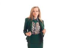 Chica joven atractiva con el pelo rubio que presenta para la cámara en una chaqueta verde y una falda Fotografía de archivo libre de regalías