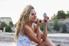 Chica joven atractiva con el pelo rubio rizado que pone un lápiz labial Imagen de archivo