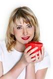 Chica joven atractiva con la taza roja Fotos de archivo libres de regalías