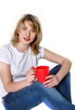 Chica joven atractiva con la taza roja Foto de archivo
