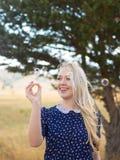 Chica joven atractiva con las jabón-burbujas en naturaleza Fotografía de archivo libre de regalías