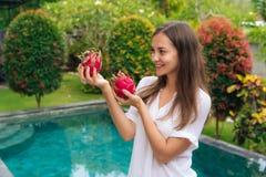 Chica joven atractiva del retrato que sostiene dos frutas del dragón, pitaya en sus manos cerca de la piscina foto de archivo