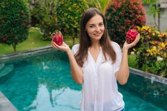 Chica joven atractiva del retrato que sostiene dos frutas del dragón, pitaya en sus manos cerca de la piscina imagenes de archivo