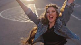 Chica joven atractiva en chaqueta de los vaqueros, con el pelo muy largo riendo, saltando y corriendo, vuelta a la cámara y sonri metrajes