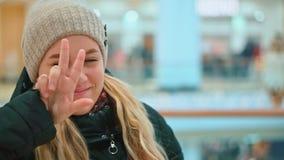 Chica joven atractiva en el sombrero del invierno que mira la cámara y la sonrisa Centro comercial almacen de video
