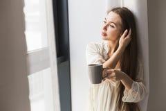 Chica joven atractiva en la ropa de noche que hace una pausa la ventana con una taza de caf? imágenes de archivo libres de regalías