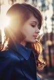 Chica joven atractiva en rayos de la puesta del sol de la calle de la ciudad Imagen de archivo