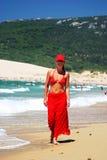 Chica joven atractiva en sarong, bikiní y gorra de béisbol rojos recorriendo a lo largo de la playa arenosa blanca apretada Imagenes de archivo