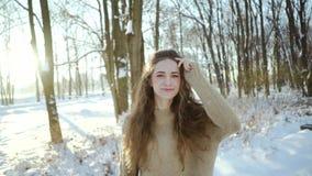 Chica joven atractiva en un suéter que se divierte en el frío Mujer joven rizada en ropa caliente en un fondo de un nevoso almacen de metraje de vídeo
