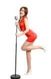 Chica joven atractiva en una alineada roja que canta en un micrófono Imagen de archivo