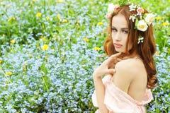 Chica joven atractiva hermosa con el pelo rojo largo con las flores en su pelo, sentándose en un campo en flores azules Imagen de archivo
