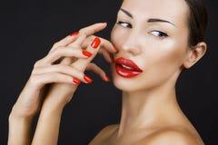 Chica joven atractiva hermosa con los labios rojos y el esmalte de uñas rojo fotografía de archivo libre de regalías