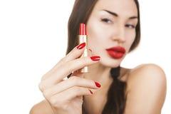 Chica joven atractiva hermosa que sostiene el lápiz labial rojo, maquillaje brillante fotos de archivo libres de regalías