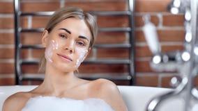 Chica joven atractiva linda confiada que disfruta de la máscara hidratante de la belleza en la cara que toma el primer del baño almacen de video
