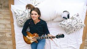 Chica joven atractiva que aprende jugar mentira de la guitarra eléctrica en cama en dormitorio en casa dentro Imágenes de archivo libres de regalías