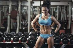 Chica joven atractiva que descansa después de ejercicios de las pesas de gimnasia Fotos de archivo
