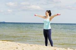 Chica joven atractiva que ejercita con pesas de gimnasia en una playa en el verano Imagen de archivo