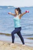 Chica joven atractiva que ejercita con pesas de gimnasia en una playa en el verano Imagen de archivo libre de regalías