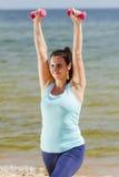 Chica joven atractiva que ejercita con pesas de gimnasia en una playa en el verano Fotos de archivo