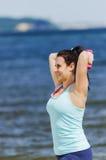 Chica joven atractiva que ejercita con pesas de gimnasia en una playa en el verano Fotos de archivo libres de regalías