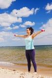 Chica joven atractiva que ejercita con pesas de gimnasia en una playa en el verano Imagenes de archivo