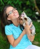Chica joven atractiva que juega con su perrito o del terrier de Yorkshire Fotografía de archivo libre de regalías