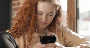 Chica joven atractiva que manda un SMS del smartphone metrajes