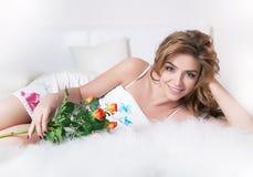 Chica joven atractiva que miente en la cama blanca con las flores Imágenes de archivo libres de regalías