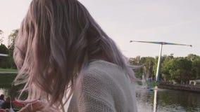 Chica joven atractiva que mira en el bolso cerca de la charca el parque del amusment almacen de metraje de vídeo